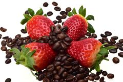 Fraises mûres d'été avec les feuilles vertes parmi des grains de café aromatique photographie stock libre de droits