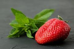 Fraises m?res et d?licieuses Plan rapproch? rouge de baie de fraise et feuille en bon ?tat sur une table concr?te noire images stock