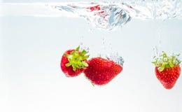 Fraises rouges de fruit frais tombant dans l'eau avec l'éclaboussure sur le fond blanc, la fraise pour la santé et le régime, nut Image libre de droits