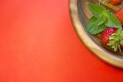 Fraises rouges et une feuille en bon état dans un plat en bois Photos libres de droits