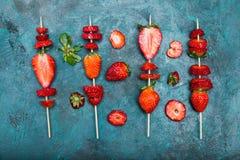 Fraises rouges fraîches entières et fraises coupées en tranches sur les brochettes en bois Photos stock