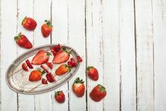 Fraises rouges fraîches entières et fraises coupées en tranches sur les brochettes en bois dans le plat de vintage sur le dessus  Photo stock