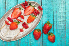 Fraises rouges fraîches entières et fraises coupées en tranches sur les brochettes en bois dans le plat de vintage sur le dessus  Photographie stock libre de droits