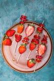 Fraises rouges fraîches entières et fraises coupées en tranches sur les brochettes en bois dans le plat en céramique Photos libres de droits