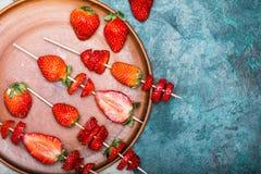 Fraises rouges fraîches entières et fraises coupées en tranches sur les brochettes en bois dans le plat en céramique Images stock