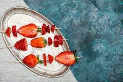 Fraises rouges fraîches entières et fraises coupées en tranches sur les brochettes en bois du plat de vintage Images stock