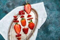 Fraises rouges fraîches entières et fraises coupées en tranches sur les brochettes en bois du plat de vintage Photo stock