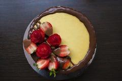 Fraises sur une soucoupe sur le fond d'un gâteau au fromage standDecorated en bois de fraise avec une tasse de thé et de fraises photo stock