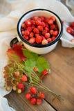 Fraisiers communs frais dans une tasse sous forme de coeur, symbole de l'amour Fond en bois La vue à partir du dessus Photos libres de droits