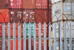 Frakta behållare bak ett staket som överträffas med taggtråd på porten av Southampton, UK Januari 2019 arkivfoto