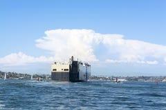 Fraktbåt som vägledas av bogserbåtar Royaltyfri Foto
