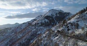 Framåt flyg- bästa sikt längs vägen på det vita snöberget i vinter Forest Woods Snöig establisher för berggatabana lager videofilmer