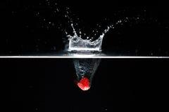 A framboesa cai profundamente sob a água com um respingo grande imagem de stock royalty free