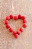 Framboesa em um coração do og da forma no fundo de madeira Foto de Stock Royalty Free