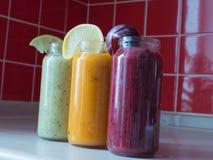 Framboesa fresca, banana, espinafres e bebidas alaranjadas na tabela de madeira Foto de Stock