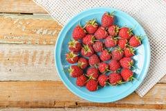 Framboesa vermelha no prato azul e na frente da tela branca em vi velho Imagens de Stock Royalty Free