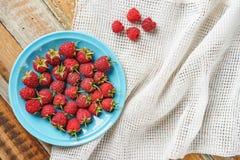 Framboesa vermelha no prato azul e na frente da tela branca em vi velho Imagem de Stock Royalty Free