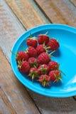 Framboesa vermelha no prato do verde azul na tabela de madeira do vintage velho Fotografia de Stock Royalty Free