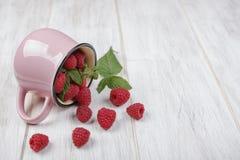 Framboesas e a caneca cor-de-rosa Fotografia de Stock