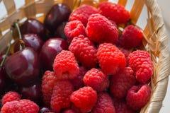Framboesas e close-up das cerejas Cesta de fruto fresco fotos de stock