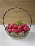 Framboesas em uma cesta no fundo de madeira rústico Imagens de Stock Royalty Free