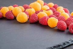 Framboesas naturais maduras vermelhas e amarelas no fundo de pedra preto Imagens de Stock Royalty Free