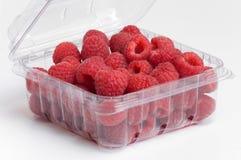 Framboesas vermelhas no recipiente plástico Foto de Stock