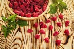 Framboises dans un plat, dans la cuvette en bois, branche de panier/buisson/élevage Photo stock