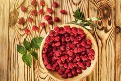 Framboises dans un plat, dans la cuvette en bois, branche de panier/buisson/élevage Images stock