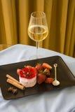Framboises de plat noir avec le verre de champagne Images stock