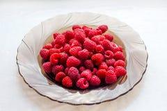 Framboises mûres savoureuses dans un plat sur un background_ blanc photos stock