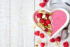 Framboos smoothie in een hartkom met superfoods, zijgrens Stock Foto