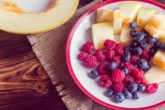 Frambozen, bosbessen en plakken van meloen Stock Afbeeldingen