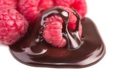 Frambozen in chocoladesaus op wit royalty-vrije stock afbeeldingen
