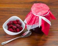 Frambozen eigengemaakte jam in een pot van glas, vruchten aan de kant met een lepel Royalty-vrije Stock Afbeelding