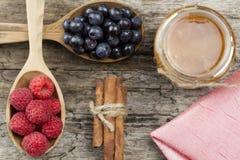 Frambozen en bosbessen in lepels met roze servet en een kruik honing met kaneel op houten achtergrond Het gezonde Eten Royalty-vrije Stock Foto's