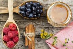 Frambozen en bosbessen in lepels met roze servet en een kruik honing met kaneel op houten achtergrond Het gezonde Eten Stock Afbeelding