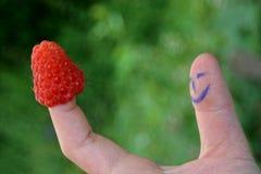 Frambozen op een vinger en een duim om onder ogen te zien stock foto's