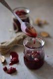 Frambozenjam die van een lepel op de lijst druipen Royalty-vrije Stock Afbeeldingen