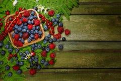 Frambuesa, arándanos y pasas en una tabla de madera vieja Visión superior Foto de archivo