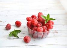 Frambuesa fresca con la menta en un fondo blanco Nutrición sana, apropiada Dieta Frutas Verano Postre imágenes de archivo libres de regalías