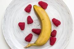 Frambuesa fresca y un plátano Fotos de archivo