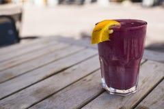 Frambuesa roja, fresa, smoothie de la fruta, con la naranja En la tabla de la terraza fotos de archivo