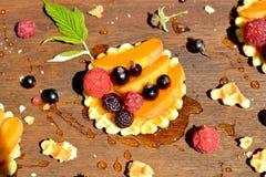 Frambuesa y pasa rojas, negras frescas, melocotón, gota de la miel en la galleta en cierre de madera del fondo para arriba Fotografía de archivo libre de regalías