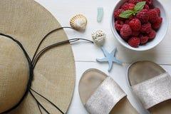 Frambuesas del concepto del verano, sombrero de paja, deslizadores y cáscaras Foto de archivo