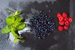 Frambuesas lavadas frescas, arándanos, hojas de menta con los waterdrops Bayas orgánicas en tablero gris de la piedra de la pizar Imagenes de archivo