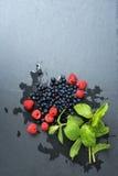Frambuesas lavadas frescas, arándanos, hojas de menta con los waterdrops Las bayas orgánicas en piedra gris de la pizarra suben,  Fotografía de archivo