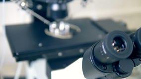 Framdel-sida sikt av ett objekt som lägger på en panel för mikroskop` s och ocularsna för instrument` s stock video