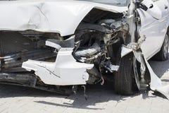 Framdelen av den vita bilen får skadad av en slump på vägen arkivbilder