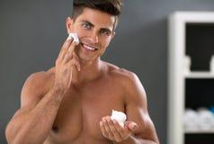 Framdelen för den unga mannen av spegeln med rakning skummar förestående Royaltyfri Fotografi